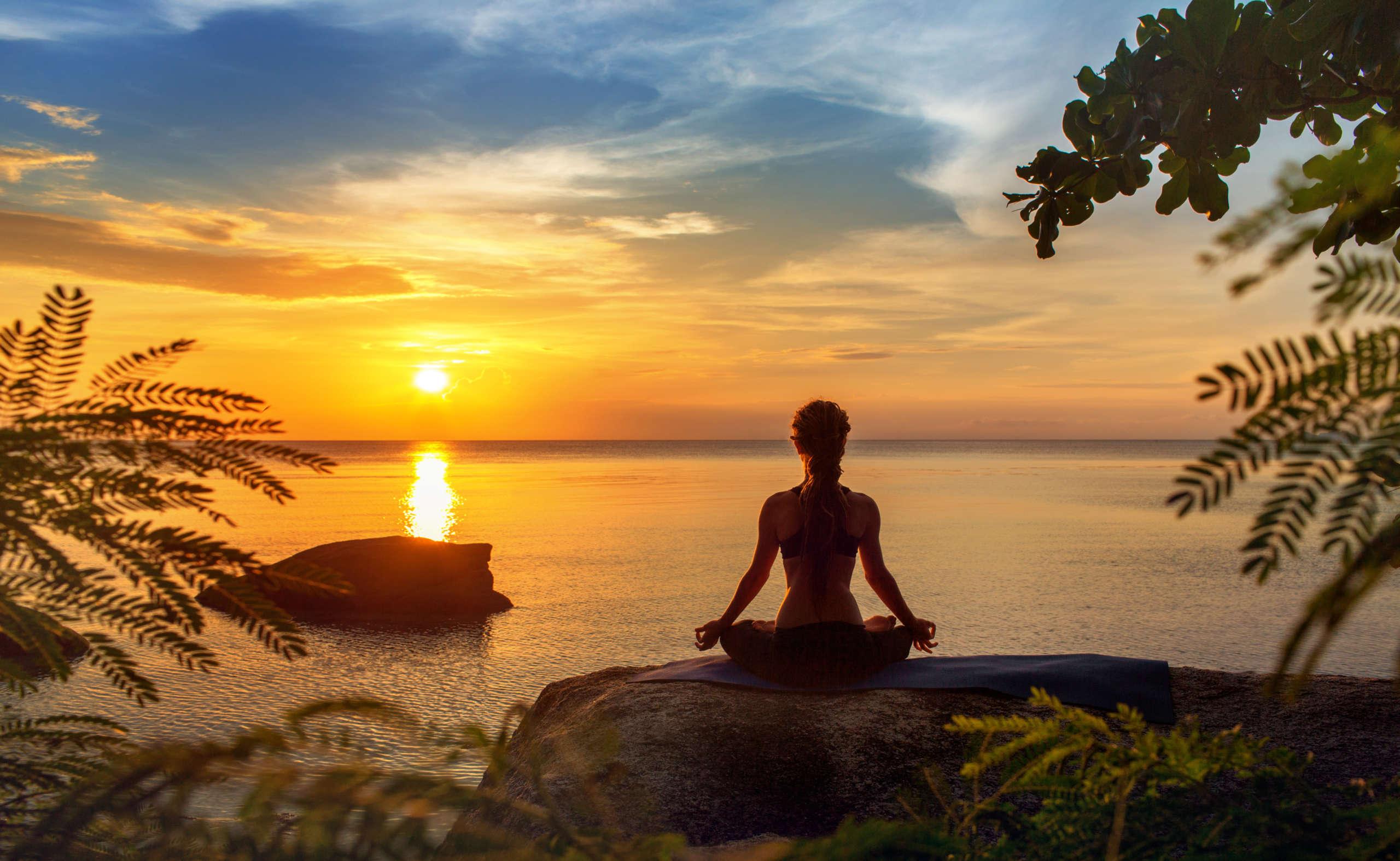 Kobieta siedząca w pozycji kwiatu lotosu na tle zachodzącego słońca - medytacja devavani