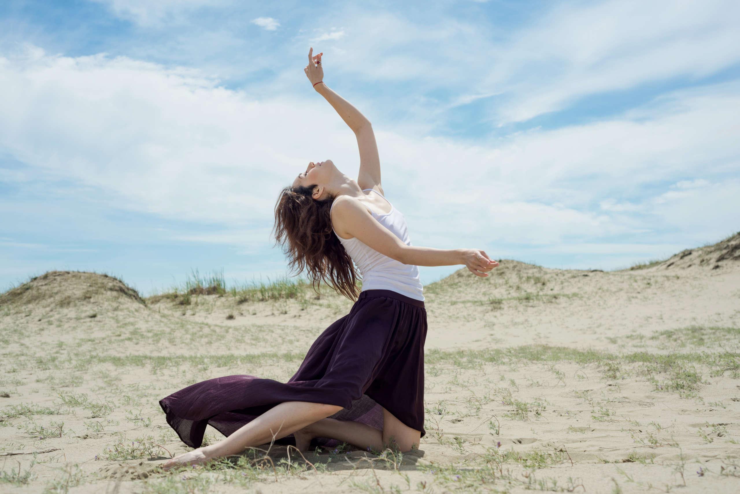 Kobieta w sukience tańcząca na polu